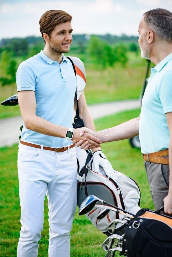 De golfspelers schudden handen met elkaar stock fotografie