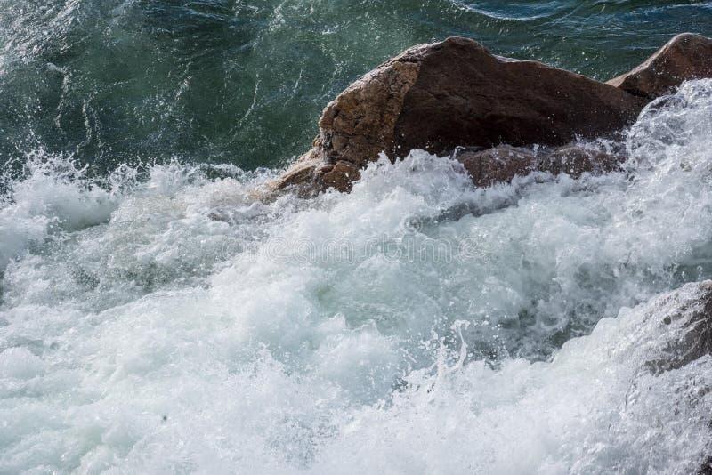 De golven die van de onweersschommeling tegen oever verpletteren royalty-vrije stock foto's