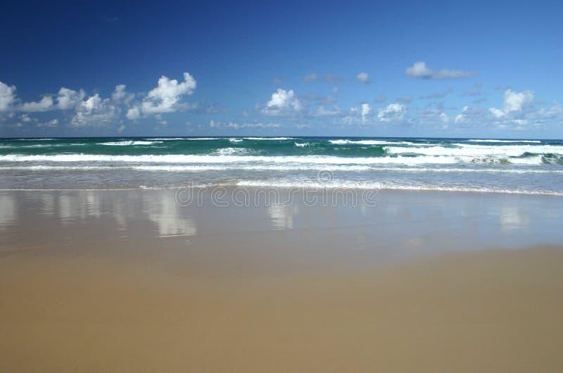 De Golven en de Branding van het zand stock afbeeldingen