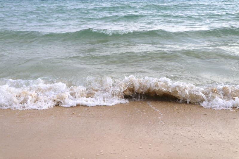 De golven in het overzees die aan de kust worden geslingerd stock afbeeldingen