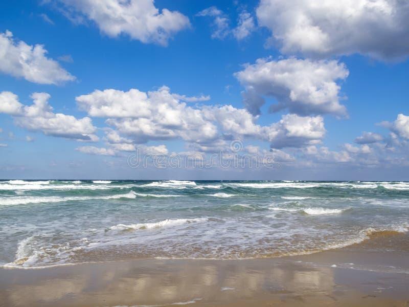 De golven op een zandig strand van de Zwarte Zee, wolkenbezinningen op het zand, cumulus worden uitgespreid betrekt in de hemel d stock fotografie