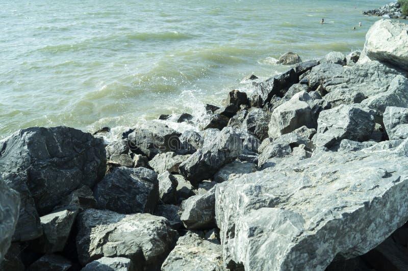 De golven van blauwe overzees worden gevonden op rotsen en neerstorting in hen stock fotografie