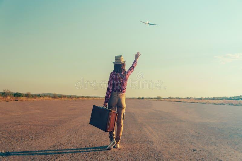 De golven van de reizigersvrouw haar hand aan vliegtuig royalty-vrije stock fotografie