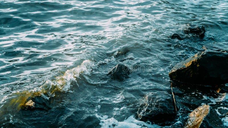 De golven van het zeewater spatten op de rotsen stock afbeelding