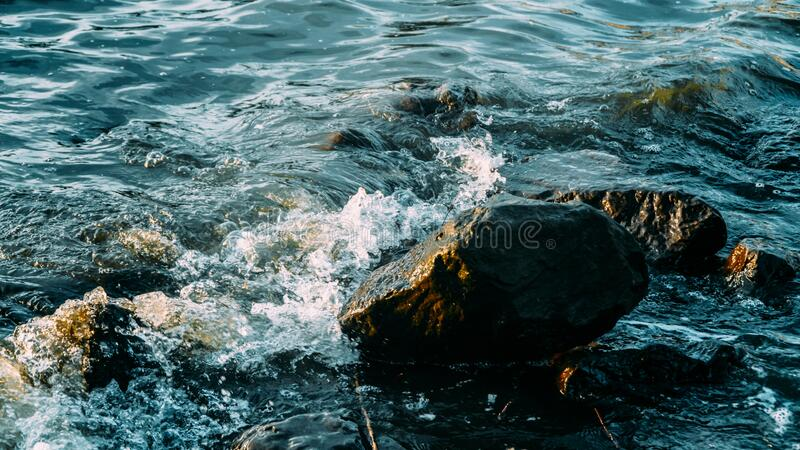 De golven van het zeewater spatten op de rotsen royalty-vrije stock fotografie