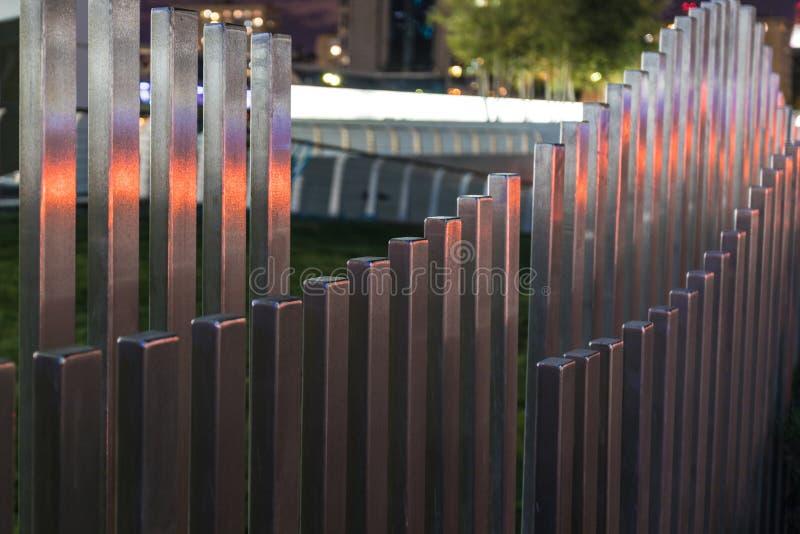De golvende houten omheining dichtbij de weg in de kleuren van autoverkeerslichten stock fotografie