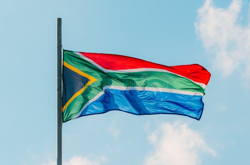 De golvende kleurrijke vlag van Zuid-Afrika op blauwe hemel stock afbeeldingen