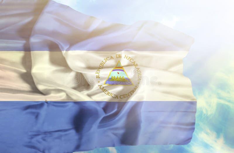 De golvende vlag van Nicaragua tegen blauwe hemel met zonnestralen stock foto
