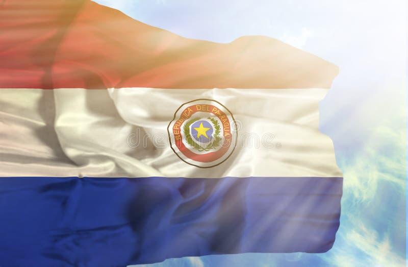 De golvende vlag van Paraguay tegen blauwe hemel met zonnestralen stock afbeelding