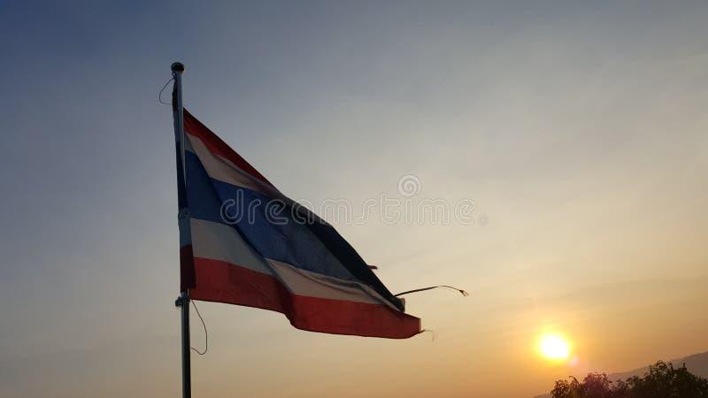De golvende vlag van Thailand met zonsondergang in de schemeringtijd stock afbeeldingen