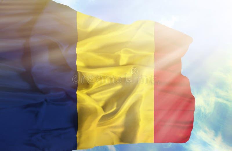 De golvende vlag van Tsjaad tegen blauwe hemel met zonnestralen stock afbeelding