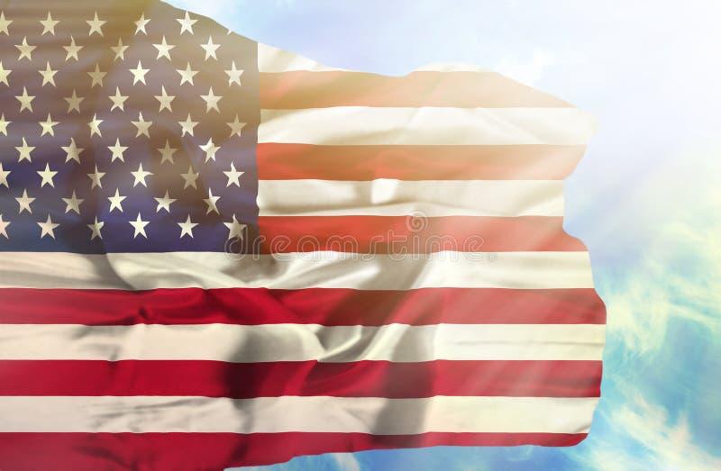 De golvende vlag van de Verenigde Staten van Amerika tegen blauwe hemel met zonnestralen royalty-vrije stock afbeeldingen