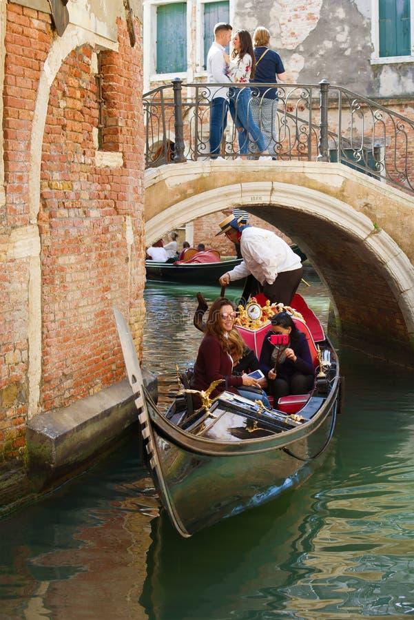 De gondel met vrolijke toeristen zwemt onder een lage romantische brug, Venetië stock foto's