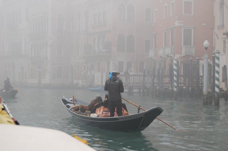 De gondelier vervoert toeristen door de kanalen van Venetië royalty-vrije stock afbeelding