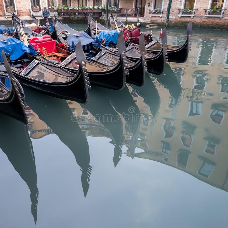 De gondels op een kanaal in Venetië, Italië worden geparkeerd die decoratieve ferro tonen/strijken bij de boog van de boten en ri stock afbeeldingen