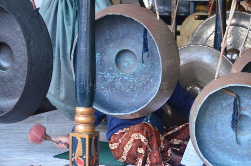 De gongslagwerker gebruikt een grote houten peddel met een dik opgevuld uiteinde zodat het geluid elegant weergalmt royalty-vrije stock afbeeldingen