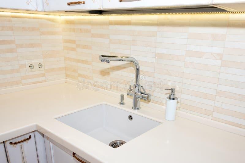 De gootsteen en de tapkraan van de keuken Moderne, heldere, schone keuken binnenlandse details royalty-vrije stock afbeelding