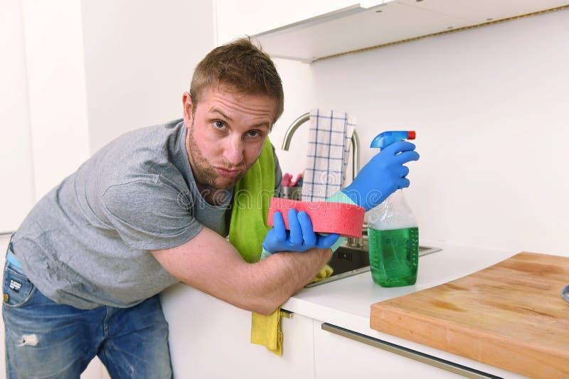De gootsteen van de jong droevig gefrustreerd mens was en het schoonmaken huiskeuken royalty-vrije stock afbeeldingen
