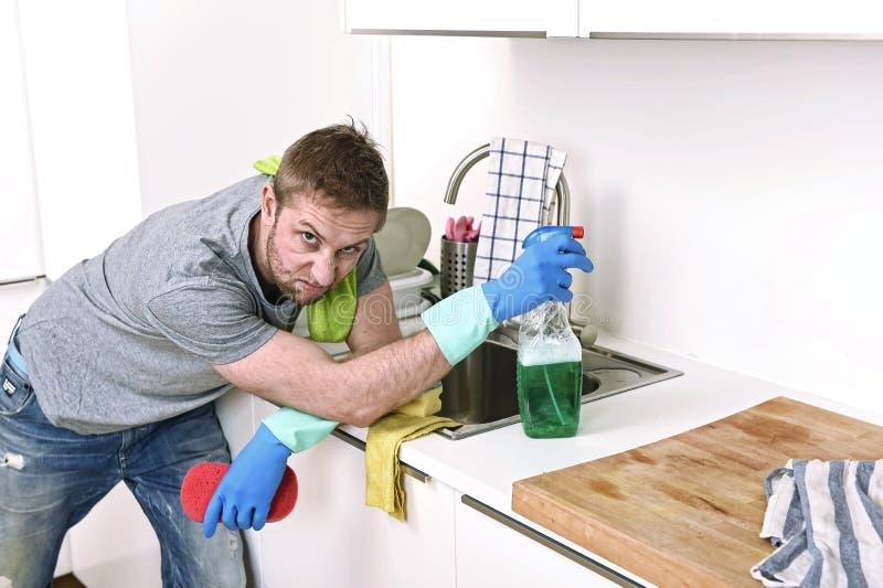De gootsteen van de jong droevig gefrustreerd mens was en het schoonmaken huiskeuken stock foto's