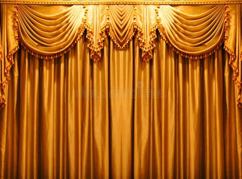 De gordijnenachtergrond van de luxe gouden stof op theate royalty-vrije stock fotografie