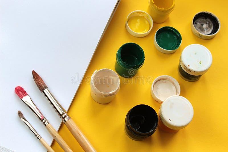 De gouacheverven en drie verschillende borstels voor het schilderen met Witboek liggen op een gele achtergrond stock foto's