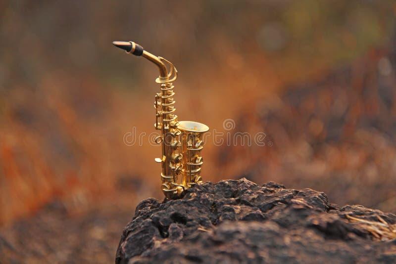 De gouden altsaxofoon bevindt zich op een zwarte steen Romantische muzikale achtergrond Muzikale dekking en creatief stock foto's