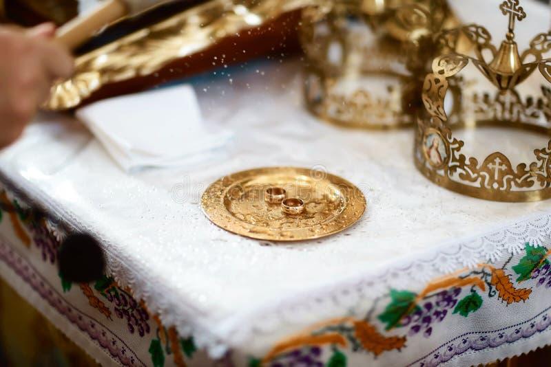 De gouden bruiloft belt dichtbij het altaar in de kerk voor het huwelijkspaar van de traditionele godsdienstige huwelijksceremoni royalty-vrije stock afbeelding