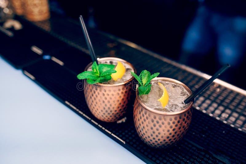 De gouden drank van de vaas exotische gezonde Cocktail met het branden van kaneel en kalk, muntdrank op een barteller Selectieve  royalty-vrije stock foto's