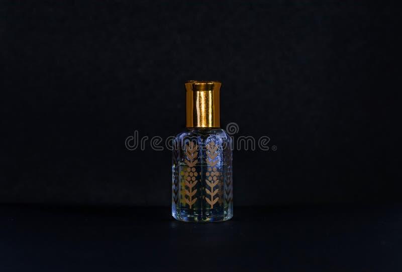 De gouden en witte fles van het Parfumglas op zwarte achtergrond stock afbeeldingen