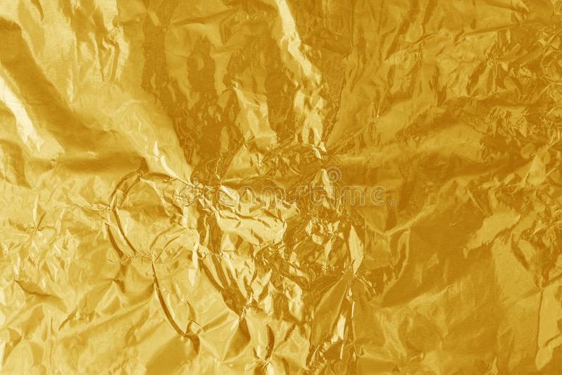 De gouden glanzende textuur van het folieblad, vat geel verpakkend document voor achtergrond samen stock foto's