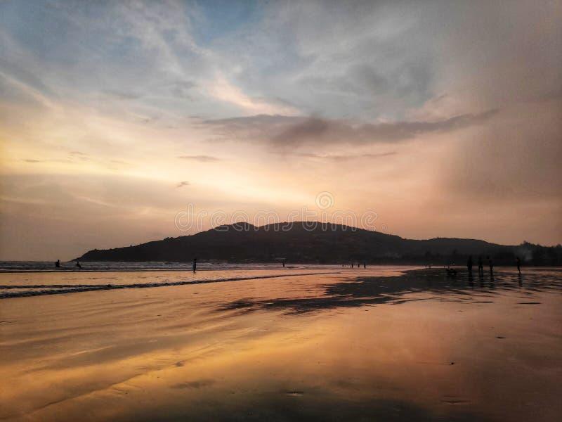 De gouden golven van de strandzonsondergang stock foto