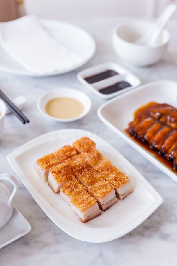 De gouden Knapperige besnoeiing van de Varkensvleesbuik in kubus diende met mosterdsaus en hete thee met eetstokjes royalty-vrije stock afbeelding