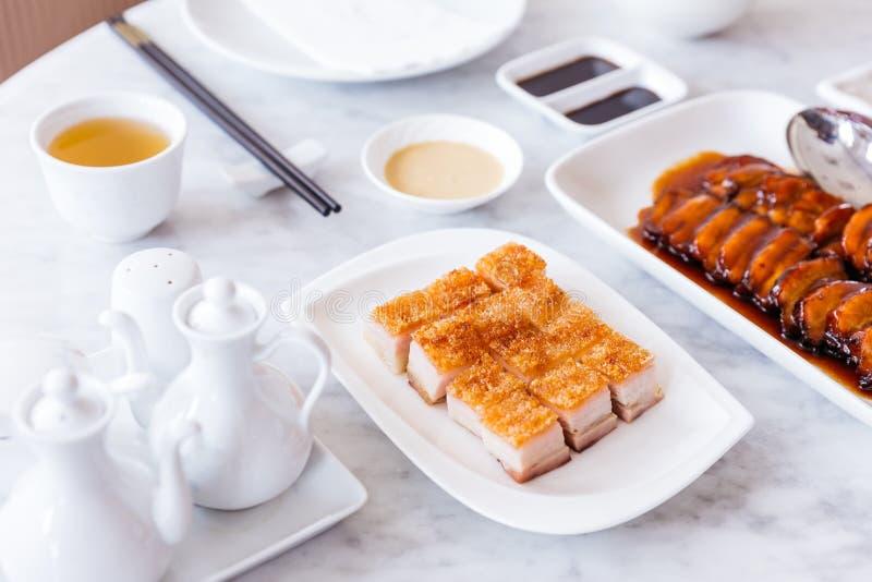 De gouden Knapperige besnoeiing van de Varkensvleesbuik in kubus diende met mosterdsaus en hete thee met eetstokjes royalty-vrije stock foto
