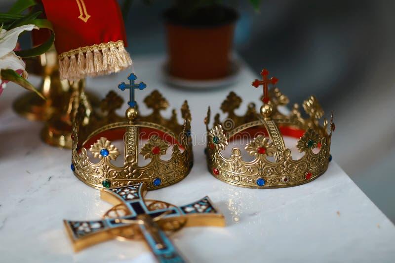 De gouden kronen en de trouwringen bij het altaar in de kerk bij het huwelijk koppelen traditionele godsdienstige huwelijksceremo stock foto