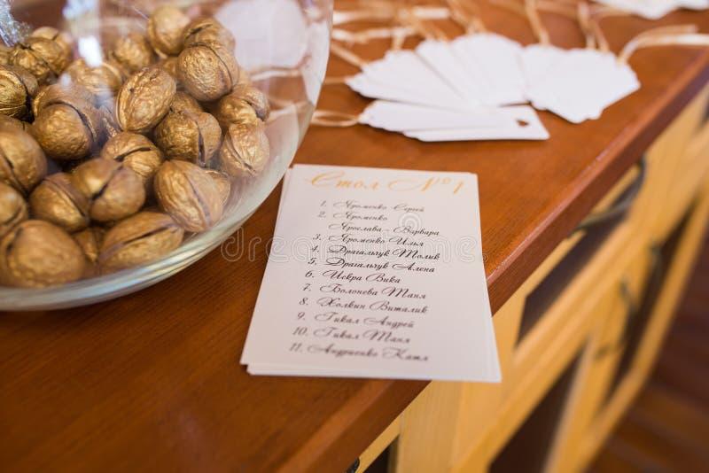 De gouden okkernoot in een glas om vaas en een gastplaatsing maken een lijst Huwelijks van decor royalty-vrije stock afbeeldingen