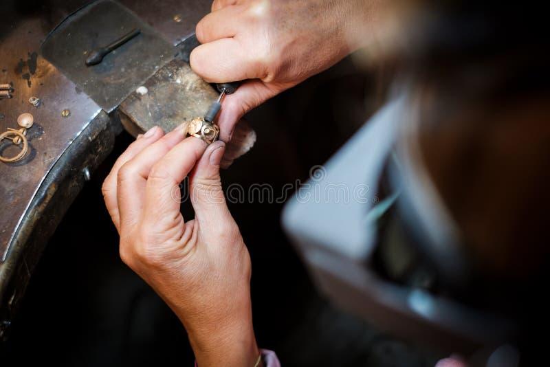 De gouden ring van juwelierpoetsmiddelen op oude werkbank in juwelenworkshop royalty-vrije stock afbeelding