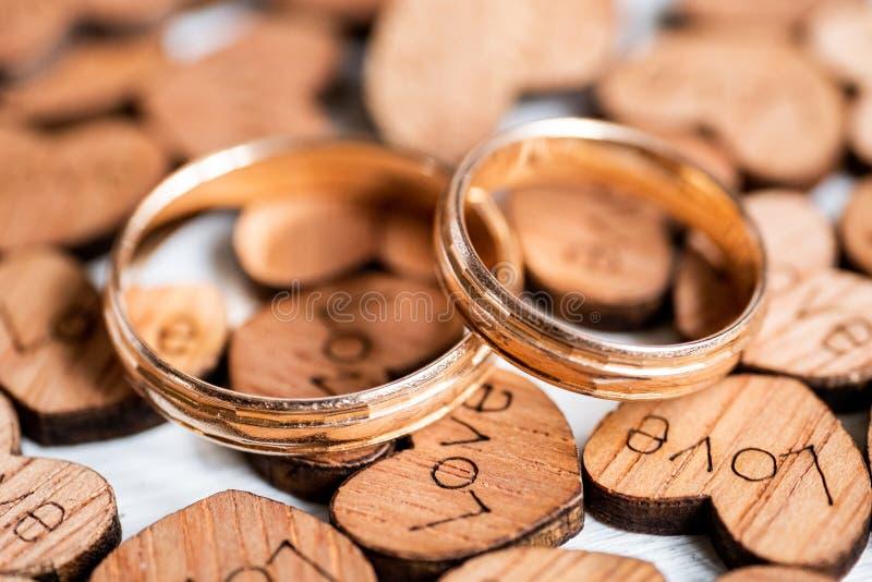 De gouden ringen van het paarhuwelijk op houten harten met geschroeide inschrijvingsliefde op witte achtergrond royalty-vrije stock afbeelding