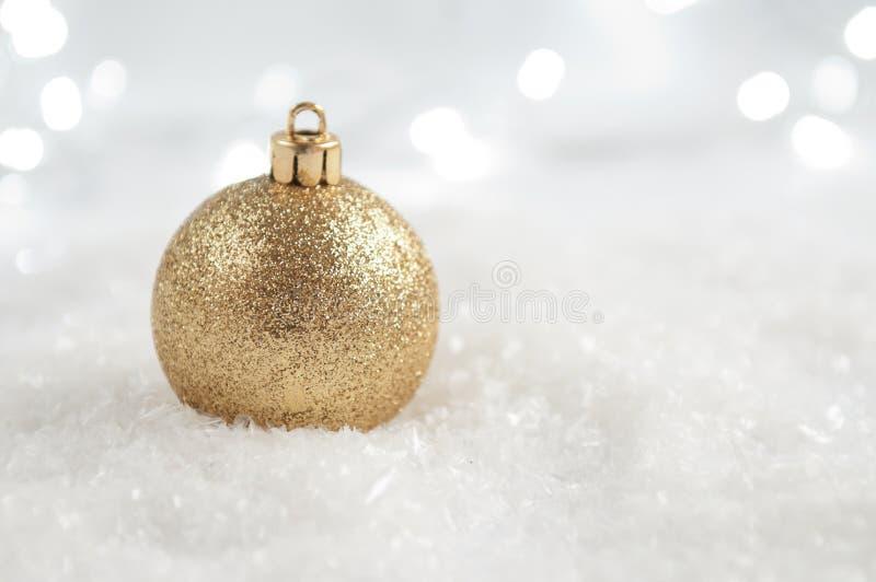 De gouden Snuisterij van Kerstmis op de Achtergrond van de Sneeuw stock afbeeldingen