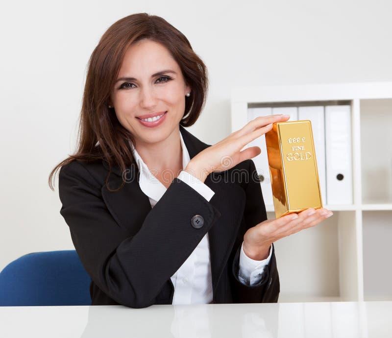 De Gouden Staaf van de Holding van de onderneemster stock foto's
