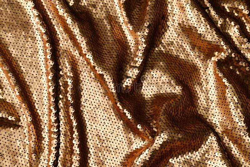 De gouden textuur van de lovertjesstof Hoogste mening stock foto's