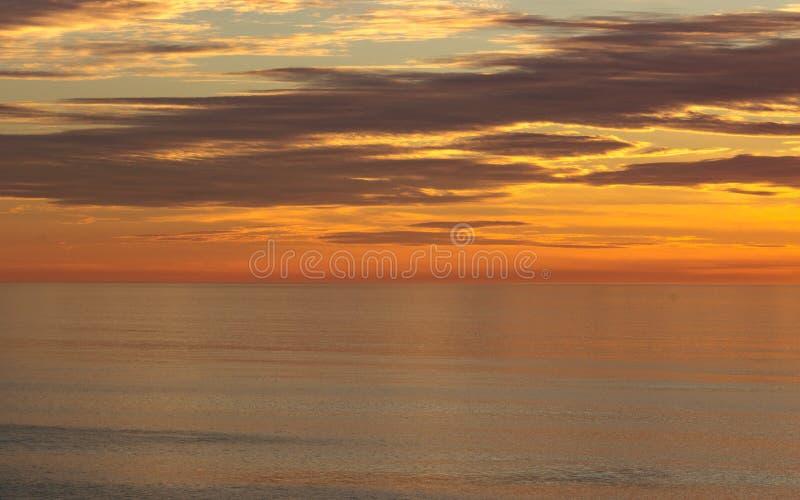 De gouden zonsondergangkleuren van oranje, gouden, blauwe wolken dachten in kalme oceaan na stock fotografie