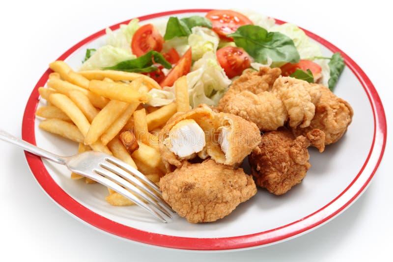 De goudklompjesgebraden gerechten en salade van vissen stock foto