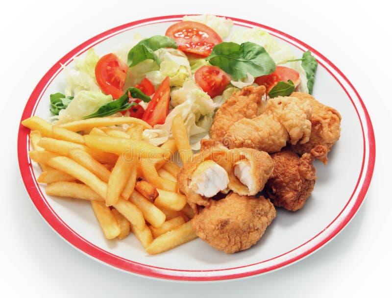 De goudklompjesgebraden gerechten en salade van vissen stock foto's