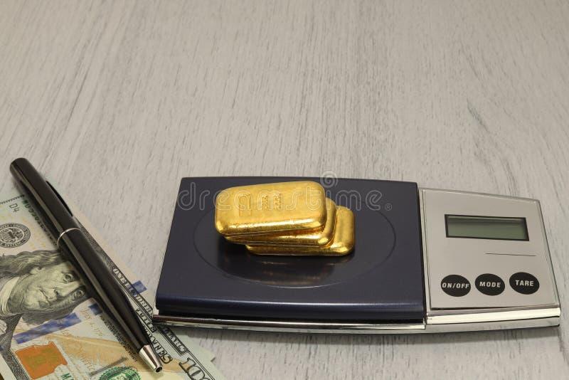 De goudstaven zijn op de schalen Een pak dollars, en een pen stock foto