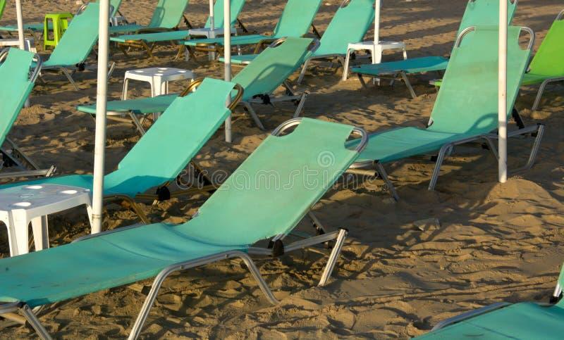 De gröna deckchairsna öppnar väntande på turister arkivfoto