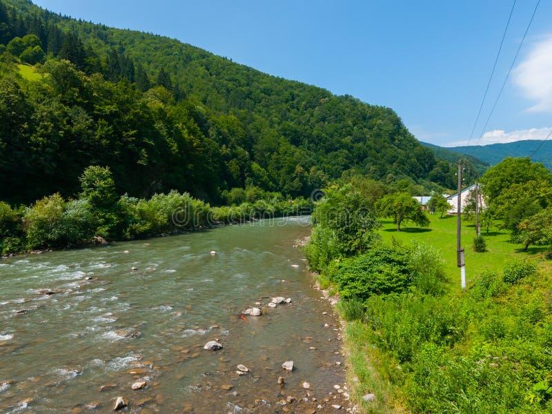 De gröna lutningarna av bergen är bevuxna med den täta skogen med strömmen som den grunda floden med vaggar på royaltyfria bilder