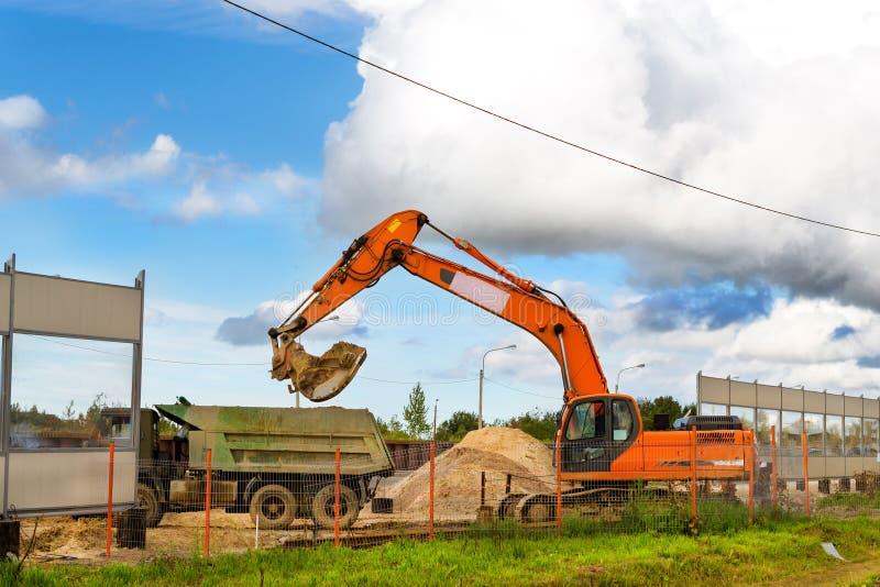 De graafwerktuigemmer laadt zware vrachtwagen met grond royalty-vrije stock foto