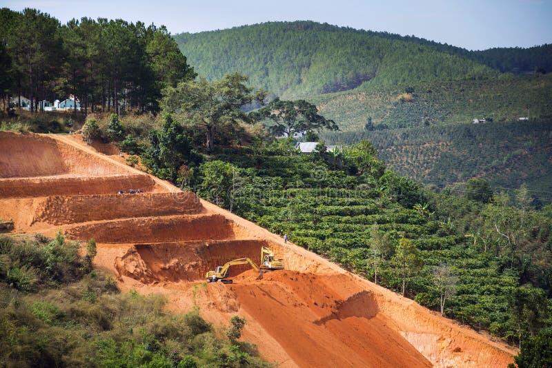 De graafwerktuigen graven terrassen voor de aanplantingen van koffiebonen in Vietnam stock afbeeldingen