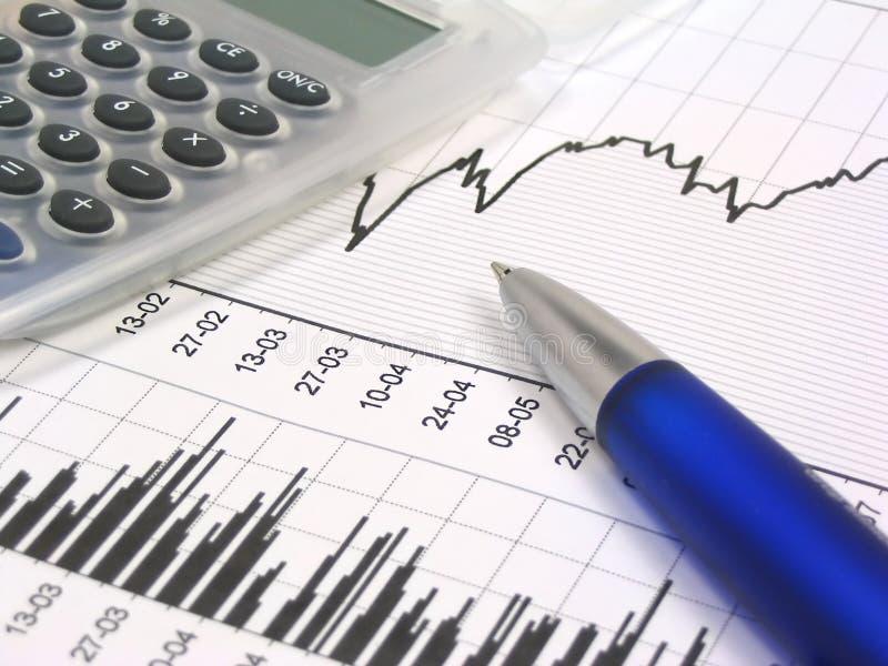 De grafiek van de voorraad met calculator en pen royalty-vrije stock afbeeldingen