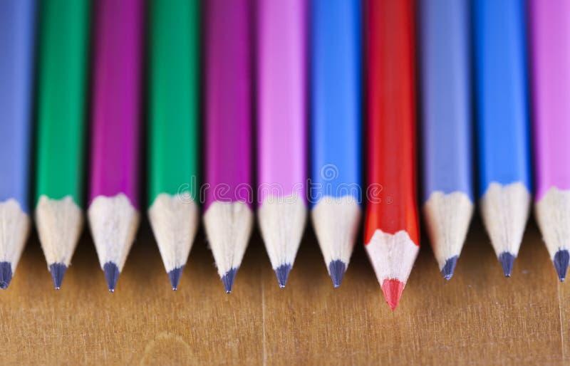 De grafietpotloden liggen op een rij, heeft één potlood een rode kern en een naar voren gebrachte, kleine diepte van scherpte stock foto's